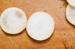 Daikon végétal découpé en tranches sur la fin en bois de planche à découper  Photographie stock libre de droits