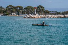 Man was sitting in a kayak, with a small motor attached, fishing royalty free stock photos