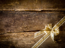 Dainty gold bow on a rustic wood background Royalty Free Stock Image