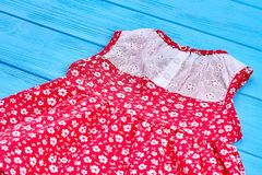 Dainty summer baby-girl dress. Red dress for little girls lying on wooden background. Toddlers cotton sleeveless dress stock photos