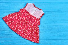 Dainty toddlers organic summer dress. Natural baby sleeveless dress and copy space, top view. Red cotton babby dress on sale stock images