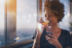 Charming black girl drinking juice and chatting using smartphone Royalty Free Stock Photos