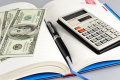 Dairy with black pen, calculator and money closeup Stock Photo
