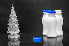 Dairy bottles and fir tree on black Royalty Free Stock Photography