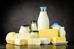 Dairy, Cheese and Milk Products. Different Types of Dairy Products with Milk, yoghurt and Cheese in Bottles and Jar on Dark Background Stock Photo