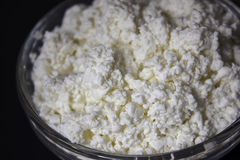 Dairy. Cottage cheese in a glass bowl. White fresh cheese in a glass bowl on a dark background. Contrast image, background Royalty Free Stock Photography