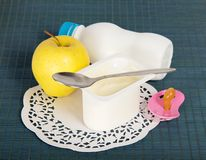 Dairy food, apple, soother and napkin. On a blue background Stock Photography
