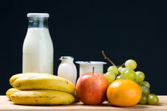 Dairy and fruit. Assorted fruits and dairy products still life on black background Royalty Free Stock Photo