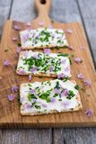 Dairy and lactose-free vegan cream cheese spread made from cashe. W and macadamia nuts on crackers with fresh chopped chives and edible chive flowers on a wooden royalty free stock photo