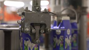 Dairy plant milk packing machine at work. Automatic milk packing device at dairy production plant in operating position close up shot stock video