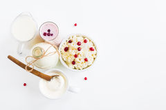 Dairy produce. Milk in bottle, cottage cheese in bowl, kefir in jar, cranberry yogurt in glass, butter and fresh berries. Stock Photos