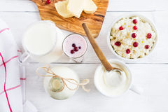 Dairy produce. Milk in bottle, cottage cheese in bowl, kefir in jar, cranberry yogurt in glass, butter and fresh berries Royalty Free Stock Images