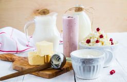 Dairy produce. Milk in bottle, cottage cheese in bowl, kefir in jar, cranberry yogurt in glass, butter and fresh berries Stock Photo