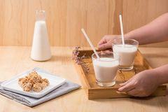 Dairy products. A bottle of milk and glass of milk serve with al. Mond candies on a wooden table Stock Photo
