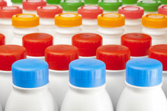 Dairy products bottles with bright covers Stock Photos