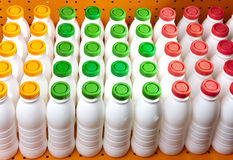 Dairy products bottles with bright covers on a shelf in the shop Royalty Free Stock Photography