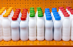 Dairy products bottles with bright covers on a shelf in the shop Stock Image