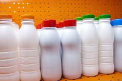 Dairy products bottles with bright covers on a shelf in the shop Stock Photo
