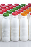 Dairy products bottles with bright covers Stock Photography