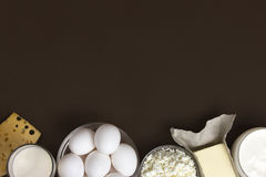 Dairy products and eggs. Background image. Space for text. Dairy products such as cheese, yogurt, cottage cheese and eggs stacked on a brown background. Space Stock Image