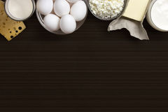 Dairy products and eggs. Background image. Space for text. Dairy products such as cheese, yogurt, cottage cheese and eggs stacked on a brown background with Royalty Free Stock Photos
