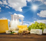 Dairy products. Photo of milk, cheese, fruit and pepper on wooden desk with blue sky Royalty Free Stock Image