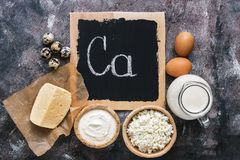 Dairy products rich in calcium on a rustic background. Signboard with text. Flat lay, copy space. stock photography