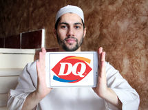 Dairy Queen, DQ fast food restaurant logo. Logo of  Dairy Queen, DQ fast food restaurant on samsung tablet  holded by arab muslim man Royalty Free Stock Image