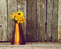 Daisies in an antique vase on wood. Stock Photo