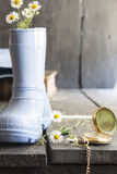 Daisies in a boot and pocket watch, flower background Royalty Free Stock Photos