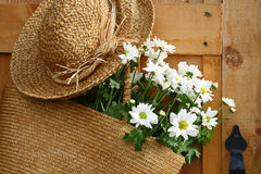Daisies in summer purse. Freshly picked daisies hanging in a summer purse with old summer hat Royalty Free Stock Images
