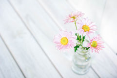 Daisies in vase on a old wooden table Stock Images