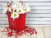 Daisy bouquet in red polka dot gift bag Stock Photos