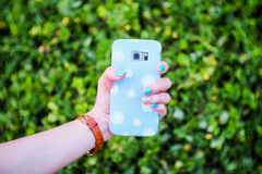 Daisy flower phone case and hand with blue nails. Stock Photography