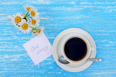 Daisy flowers and cup of tea with good morning note Stock Photo