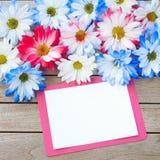 Daisy Flowers en colores blancos y azules rojos con la tarjeta de la invitación del partido que pone en la tabla rústica del tabl fotografía de archivo libre de regalías