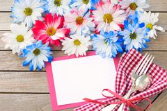 Daisy Flowers in Red White and Blue Colors with Party Invitation Card Laying on Rustic Board Table with room or space for your wor. Ds, text, or copy.  A flat Royalty Free Stock Photography