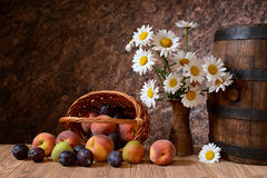 Daisy flowers in a vase with fresh fruits in a vicker basket stock images
