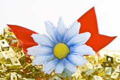 Daisy with gold stars. A closeup of a fake blue-white daisy with a foam ribbon lying on a sea of golden pieces with star-shaped cut outs Royalty Free Stock Images