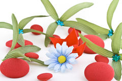 Daisy and Leaves. A fake daisy (blue-white) and leaves interspread with red pebbles on a white surface Royalty Free Stock Images