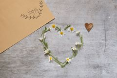 Daisy love symbol on old wooden background. Envelope with flowers and an inscription happy royalty free stock image
