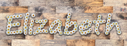 Daisy Name Elizabeth Wood Background. Name made from real daisy flowers on wood background Royalty Free Stock Images