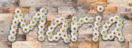 Daisy Name Maria Wood Background. Name made from real daisy flowers on wood background Royalty Free Stock Images