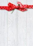 Daisy in polka dot bow on wood Royalty Free Stock Photography