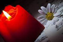 Daisy and Red Candle on Music Notes Sheet Stock Photo