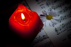 Daisy and Red Candle on Music Notes Sheet Royalty Free Stock Image