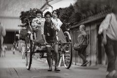 Daiunin, Kyoto, Japan - October 18, 2016 : RICKSHAW MAN, THE ENTERTAINER. Rickshaw driver entertains his passengers during a ride through a shopping alley near Stock Photography