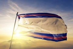 Dajabon Province of Dominican Republic flag textile cloth fabric waving on the top sunrise mist fog. Beautiful royalty free stock image