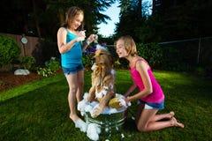 Daje skąpaniu dwa młodej dziewczyny ich psu Fotografia Royalty Free