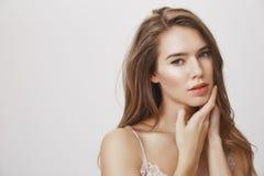 Daje twój skórze koniecznej opiece Studio strzał atrakcyjny europejski kobieta model delikatnie dotyka twarz, ono wpatruje się se zdjęcie royalty free